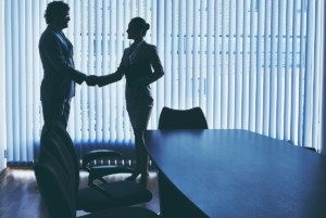 Woman & Man Shaking Hands Over Guaranteed Business Loans
