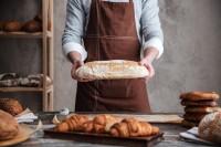 Man baker holding bread - Bakery Business Plan